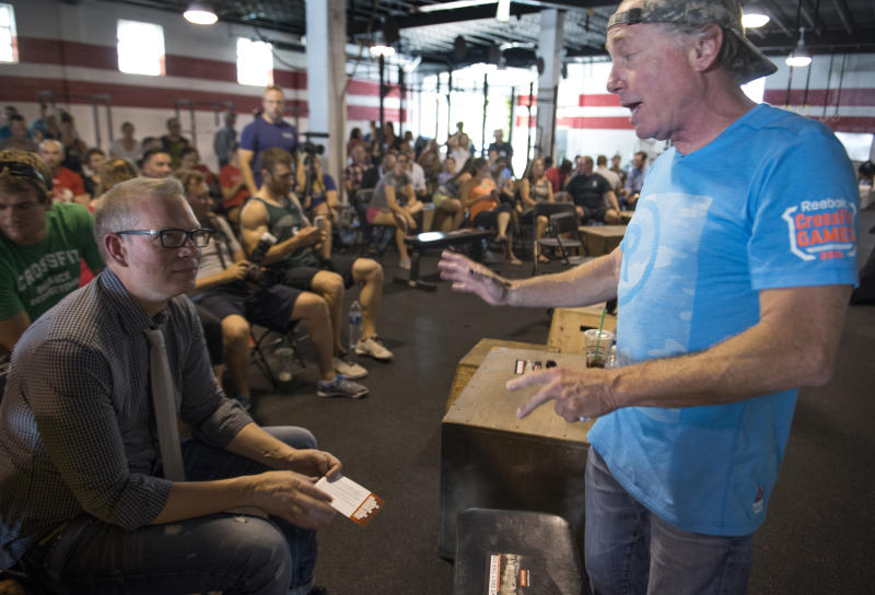 WASHINGTON, DC - JULY 31: Crossfit Inc. founder and CEO Greg Glassman (R) talks to employees prior to a presentation at the Half street location in Washington, DC on July 31, 2015. CrossFit is waging a war against new DC rules to regulate personal trainers, saying D.C. is a pawn in a commercial fight over personal fitness. The city council is proposing licensure and regulation of personal trainers. There is a fee involved. If the law should pass, DC would be the first municipality in the nation to do so. Crossfit Inc. officials are fighting the proposed law and say that they are trying to legislate something that they do not understand. (Photo by Linda Davidson / The Washington Post via Getty Images)