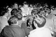 FILE - Boston Celtics' Tommy Heinsohn, center, is swarmed by fans after the Celtics defeated the St. Louis Hawks to win the NBA championship in Boston, in this April 13, 1957, file photo. Tommy Heinsohn, who as a Boston Celtics player, coach and broadcaster was with the team for all 17 of its NBA championships, has died. He was 86. The team confirmed Heinsohn's death on Tuesday, Nov. 10, 2020. (AP Photo, File)