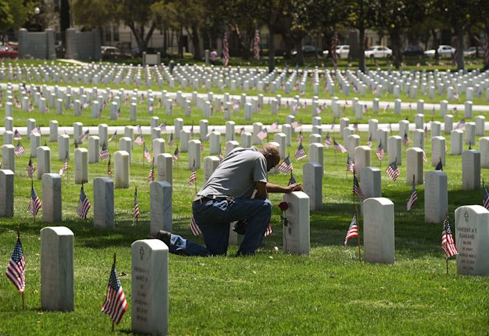 <p>Navy veteran Richard Jones prays before the grave of his friend James McDermott at the Los Angeles National Military Cemetery two days prior to Memorial Day in Los Angeles, Calif., on May 26, 2018. (Photo: Mark Ralston/AFP/Getty Images) </p>
