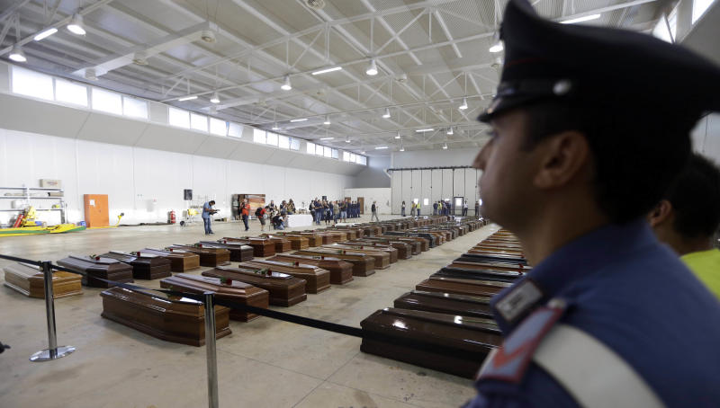 An Italian Carabiniere, paramilitary police man, stands near the coffins of died immigrants inside a hangar of Lampedusa's airport, Italy, Saturday, Oct. 5, 2013. A ship carrying African migrants towards Italy sank Thursday after a fire was set onboard to attract attention of any passing boats or people on shore when they ran into trouble. They had traveled for two full days and thought they had reached safety when they saw the lights of Lampedusa. Instead, at least 111 drowned and 155 survived, some of whom were in the water for three hours, clinging to anything buoyant, even empty water bottles. (AP Photo/Luca Bruno)