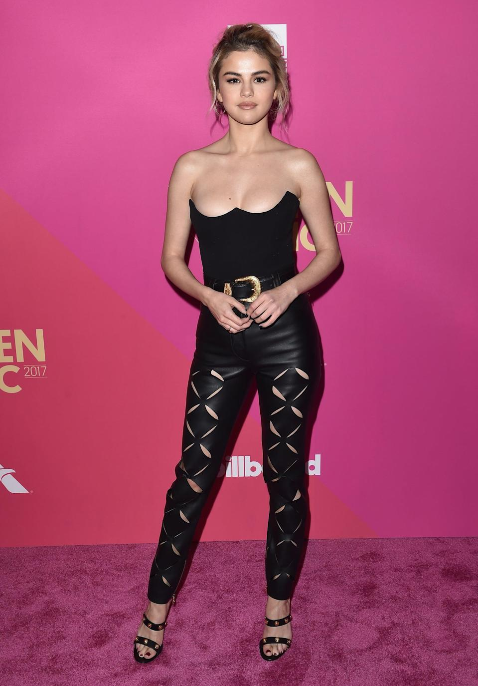 """<p>Selena turned up the heat in <a href=""""https://www.popsugar.com/fashion/Selena-Gomez-Versace-Leather-Outfit-Billboard-Music-Awards-44319064"""" class=""""link rapid-noclick-resp"""" rel=""""nofollow noopener"""" target=""""_blank"""" data-ylk=""""slk:all-black Versace"""">all-black Versace</a> at the 2017 Billboard Women in Music Awards in California. Her cutout leather trousers drew attention downward - straight to her double-strap sandals, also by Versace, of course.</p>"""