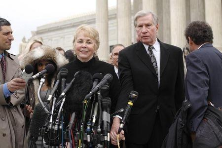 Pamela Hurst and her husband Douglas Hurst, plaintiffs against the U.S. government in the King v. Burwell case, take to the microphones to speak to reporters after arguments at the Supreme Court building in Washington, March 4, 2015. REUTERS/Jonathan Ernst