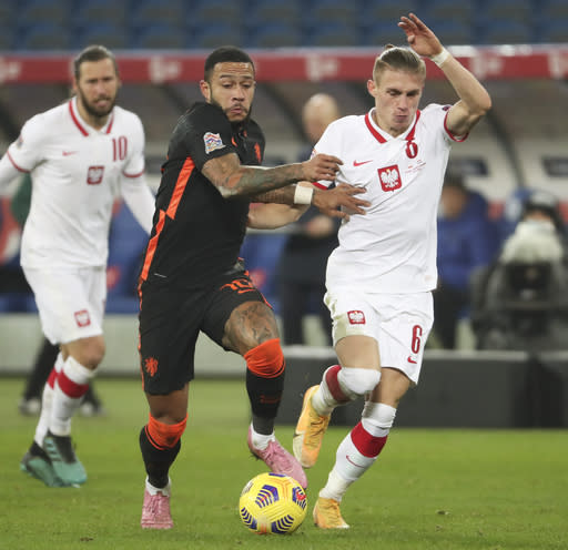 Netherlands' Memphis Depay, left, and Poland's Przemyslaw Placheta vie for the ball during the Nations League soccer match between Poland and The Netherlands at Silesian Stadium in Chorzow, Poland, Wednesday, Nov. 18, 2020. (AP Photo/Czarek Sokolowski)