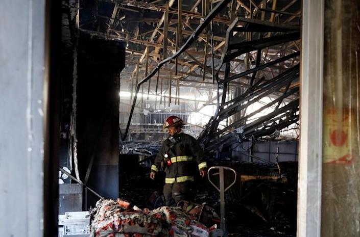 A firefighter is seen inside a burnt and looted supermarket one day after a protest against the government in Valparaiso