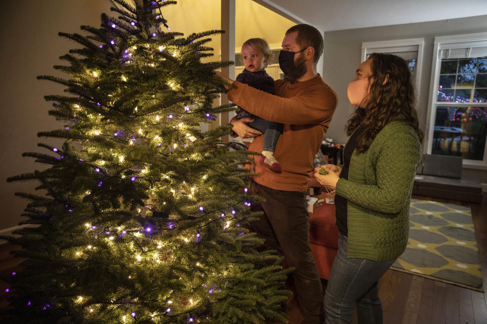 Ani Sirois places lights and decorations on the family's Christmas tree with daughter Ida, 2, and husband, Chadwick, at their home on Tuesday, Nov. 24, 2020, in Portland, Ore. (AP Photo/Paula Bronstein)
