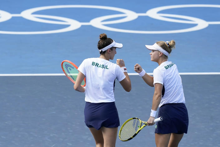 Luisa Stefani, left, and Laura Pigossi, of Brazil, speak during the women's doubles bronze medal tennis match against Veronika Kudermetova and Elena Vesnina, of the Russian Olympic Committee, at the 2020 Summer Olympics, Saturday, July 31, 2021, in Tokyo, Japan. (AP Photo/Patrick Semansky)
