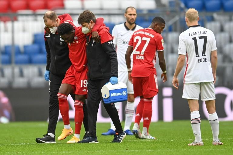 Alphonso Davies is helped off after tearing ankle ligaments on Saturday