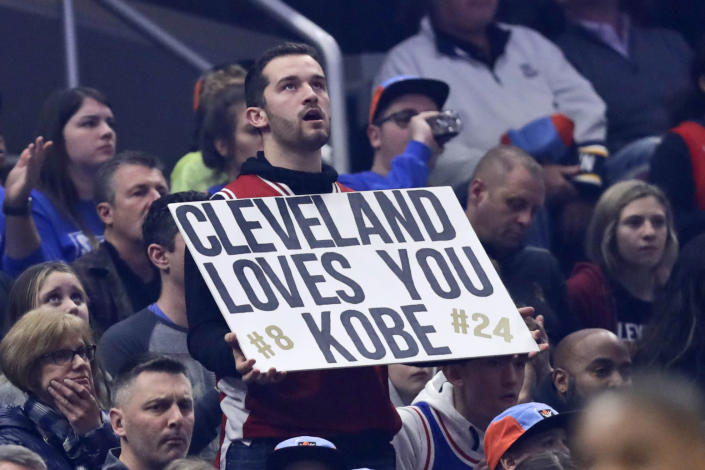 A fan holds up a sign about Kobe Bryant during the first half of an NBA basketball game between the Cleveland Cavaliers and the New Orleans Pelicans, Tuesday, Jan. 28, 2020, in Cleveland. Bryant, his 13-year-old daughter Gianna and six other passengers were killed along with the pilot Sunday. (AP Photo/Tony Dejak)