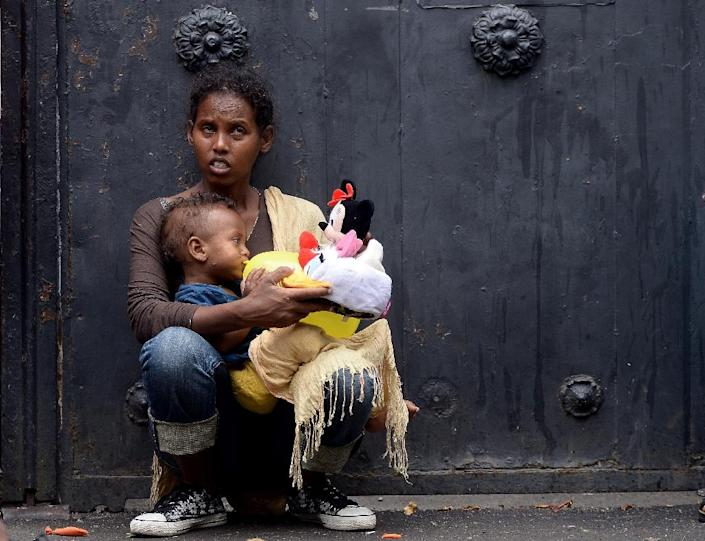 """A mother holds her child with toys brought by aid workers outside """"Baobab"""" migration centre next to the Tiburtina train station in Rome on June 14, 2015 (AFP Photo/Filippo Monteforte)"""