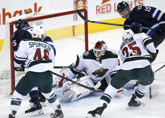 Minnesota Wild's goaltender Niklas Backstrom (32) gets a leg on Winnipeg Jets' Mark Scheifele's (55) shot as the Jets' Matt Halischuk (15) and Wild's goaltender Darcy Kuemper (35) and Jared Spurgeon (46) look for the rebound during the first period of an NHL game in Winnipeg, Manitoba, Saturday, Nov. 23, 2013. (AP Photo/The Canadian Press, John Woods)