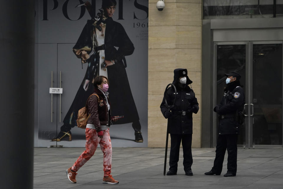 Security personnel watch over a retail street in Beijing Wednesday, March 3, 2021. The state of the world's second largest economy takes precedence among the myriad issues presented by Chinese Premier Li Keqiang in his address at the National People's Congress opening session to take place on Friday, March 5. 2021. (AP Photo/Ng Han Guan)