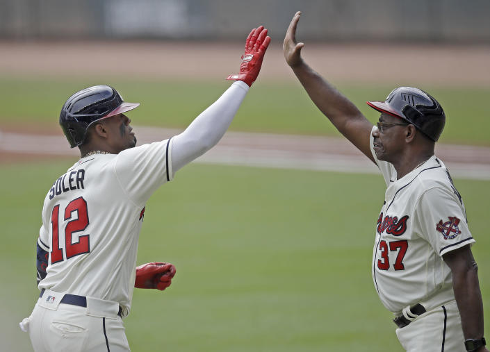 Atlanta Braves' Jorge Soler (12) is congratulated by third base coach Ron Washington, right, after hitting a home run off New York Mets pitcher Noah Syndergaard in the first inning of a baseball game Sunday, Oct. 3, 2021, in Atlanta. (AP Photo/Ben Margot)