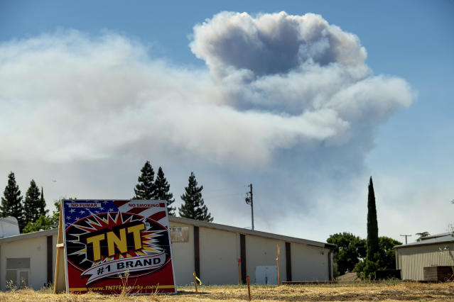 <p>A plume rises behind a building in Esparto, Calif., as a wildfire burns on July 1, 2018.(Photo: Noah Berger/AP) </p>