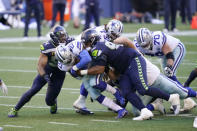 Seattle Seahawks middle linebacker Bobby Wagner, left, and defensive tackle Bryan Mone (92) tackle Dallas Cowboys running back Ezekiel Elliott (21) during the second half of an NFL football game, Sunday, Sept. 27, 2020, in Seattle. The Seahawks won 38-31. (AP Photo/Elaine Thompson)