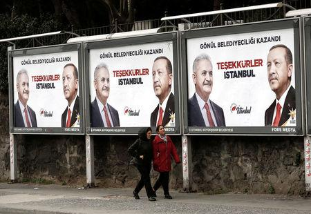 People walk past by AK Party billboards with pictures of Turkish President Tayyip Erdogan and mayoral candidate Binali Yildirim in Istanbul