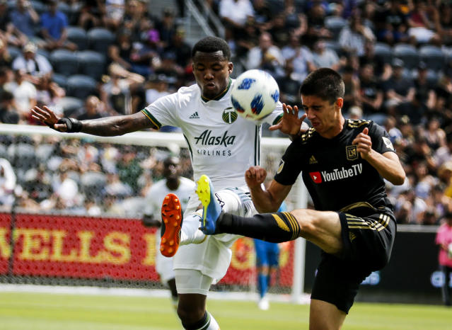 Portland Timbers defender Alvas Powell, left, of Jamaica, vies with Los Angeles FC defender Joao Moutinho, of Portugal, in the first half of an MLS soccer game in Los Angeles, Sunday, July 15, 2018. (AP Photo/Ringo H.W. Chiu)