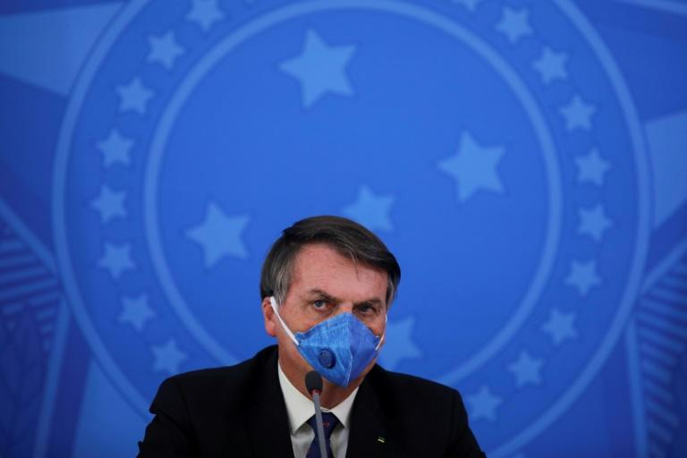 Brazil's President Jair Bolsonaro wears a face mask during a press conference on the coronavirus pandemic at the Planalto Palace in Brasilia