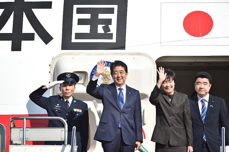 Japan's Prime Minister Shinzo Abe (2nd L) and his wife Akie (2nd R) wave to well-wishers prior to boarding a government plane at Tokyo's Haneda airport on November 17, 2016 (AFP Photo/Kazuhiro Nogi)