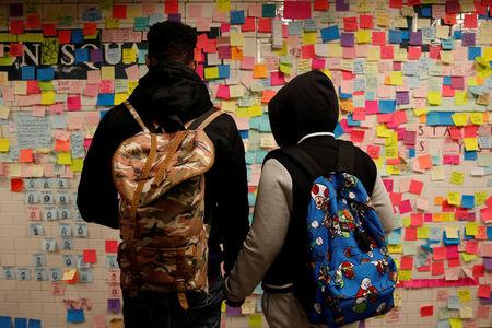 People holds hands looking at post-election Post-it notes  pasted along a tiled walk at Union Square subway station in New York U.S., November 14, 2016. REUTERS/Shannon Stapleton/File Photo