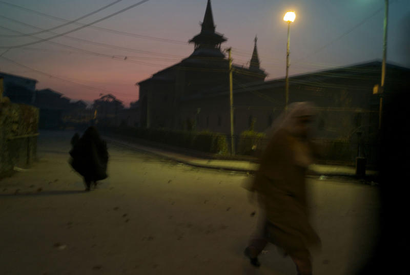 Women make their way home at dusk as clouds of tear gas engulfs the air in the stone strewn streets surrounding the Jama Masjed following riots in Srinagar in Dec. 2008. | Alixandra Fazzina—NOOR/Redux