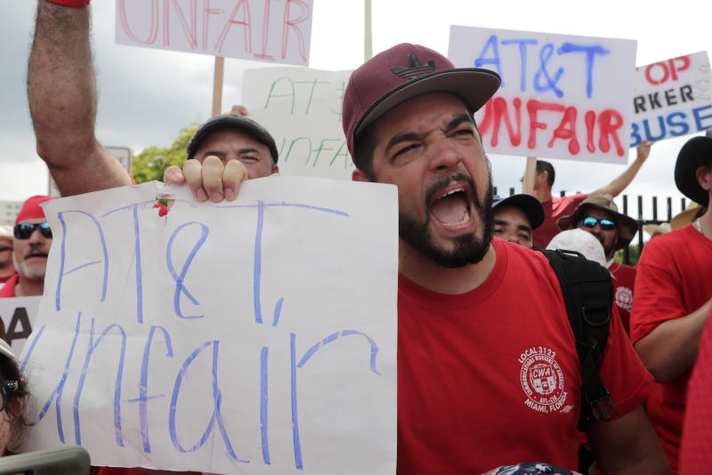 Members of the Communications Workers of America (CWA) walk a picket line outside of an AT&T office Monday, Aug. 26, 2019, in Miami. CWA union members in the southeast went on strike Friday over unfair labor practices by management during negotiations for a new contract. (AP Photo/Lynne Sladky)