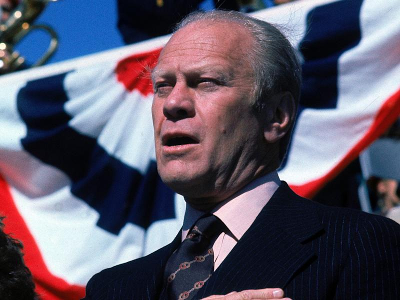 American President Gerald Ford, with his hand over his chest, sings to the accompaniment of a brass band while on the campaign trail at the Iowa State Fair, Iowa, October 1976.