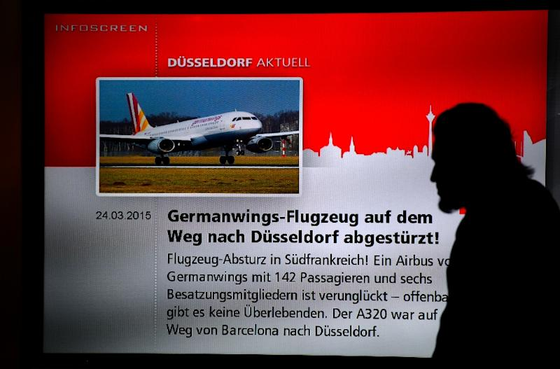 A man walks past a screen displaying news on the crash of a Germanwings plane on March 24, 2015 at the airport in Duesseldorf, western Germany, where the crashed Germanwings airplane was due to land