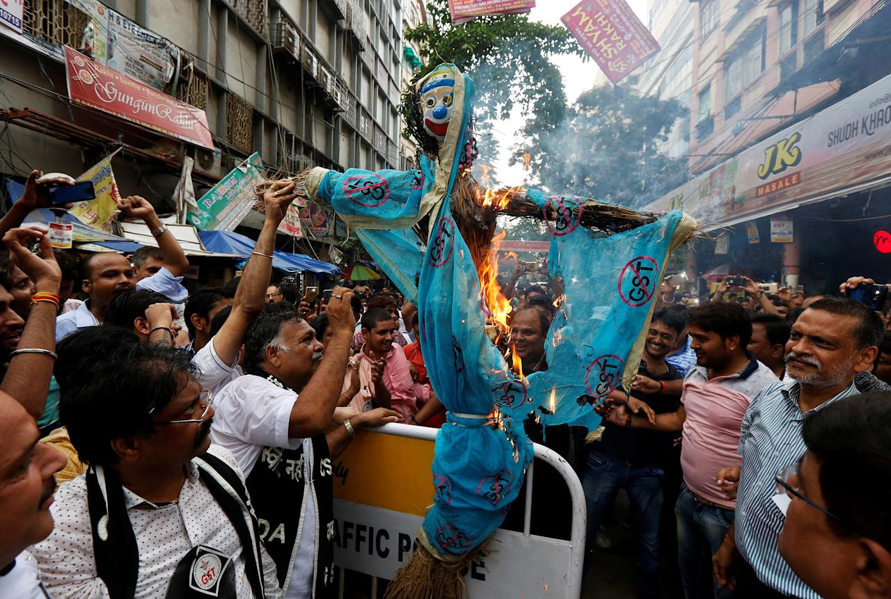 Cloth merchants and workers shout slogans as they burn an effigy depicting the Goods and Services Tax (GST) during a protest against the implementation GST on textiles, in Kolkata, India June 29, 2017. REUTERS/Rupak De Chowdhuri