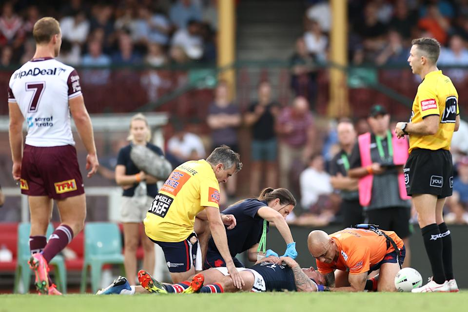 Jake Friend is attended to by team trainers after head knock during the round one NRL match between the Sydney Roosters and the Manly Sea Eagles at the Sydney Cricket Ground, on March 13, 2021