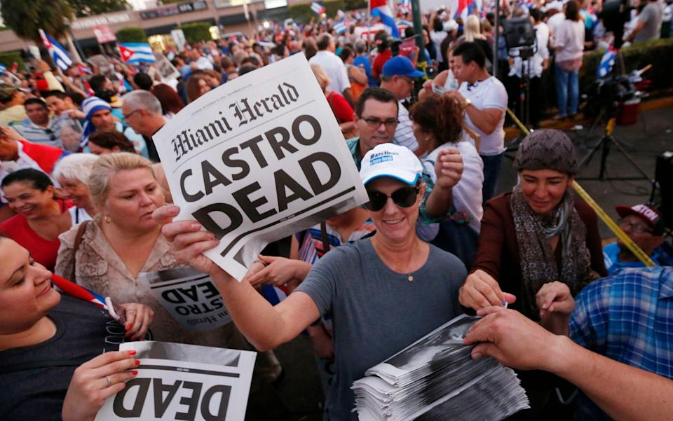 """Alexandra Villoch, president and publisher of the Miami Herald Media Company, hands out a special edition of the Miami Herald with the headline """"Castro Dead,"""" in front of the Versailles Restaurant in the Little Havana neighborhood of Miami - Wilfredo Lee/AP"""