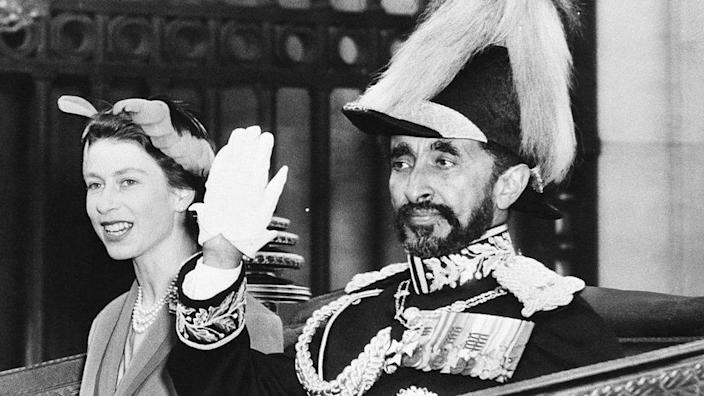 Queen Elizabeth II of England rides in an open carriage with Ethiopia's Emperor Haile Selassie. Entering Whitehall from Parliament Square on the Buckingham Palace. The Queen went to the station to welcome the Emperor as he arrived in the British capital October 15th for a three-day state visit (10/15/54)