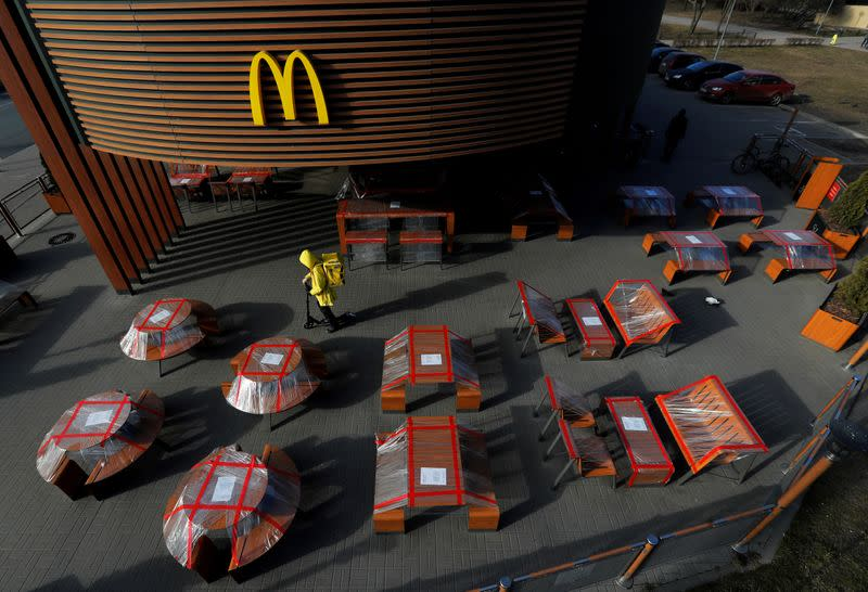 FILE PHOTO: Food delivery courier rides a scooter among plastic-wrapped tables of McDonald's restaurant in Saint Petersburg