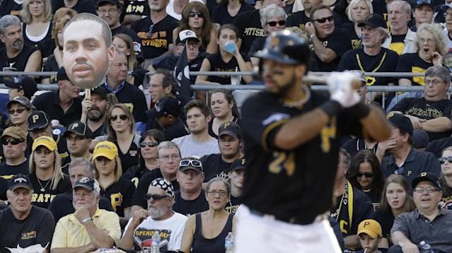A fan holds a giant poster photo of Pittsburgh Pirates' Pedro Alvarez, left, as he bats in the fourth inning of Game 3 of a National League division baseball series against the St. Louis Cardinals on Sunday, Oct. 6, 2013 in Pittsburgh. (AP Photo/Gene J. Puskar)