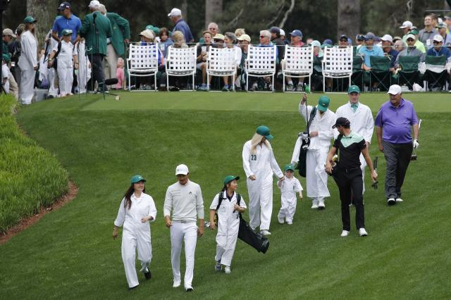 Li Haotong of China (2nd from L) and Danny Willett of England walk down the first hole with their families during the par 3 contest held on the final day of practice for the 2018 Masters golf tournament at Augusta National Golf Club in Augusta, Georgia, U.S. April 4, 2018. REUTERS/Mike Segar
