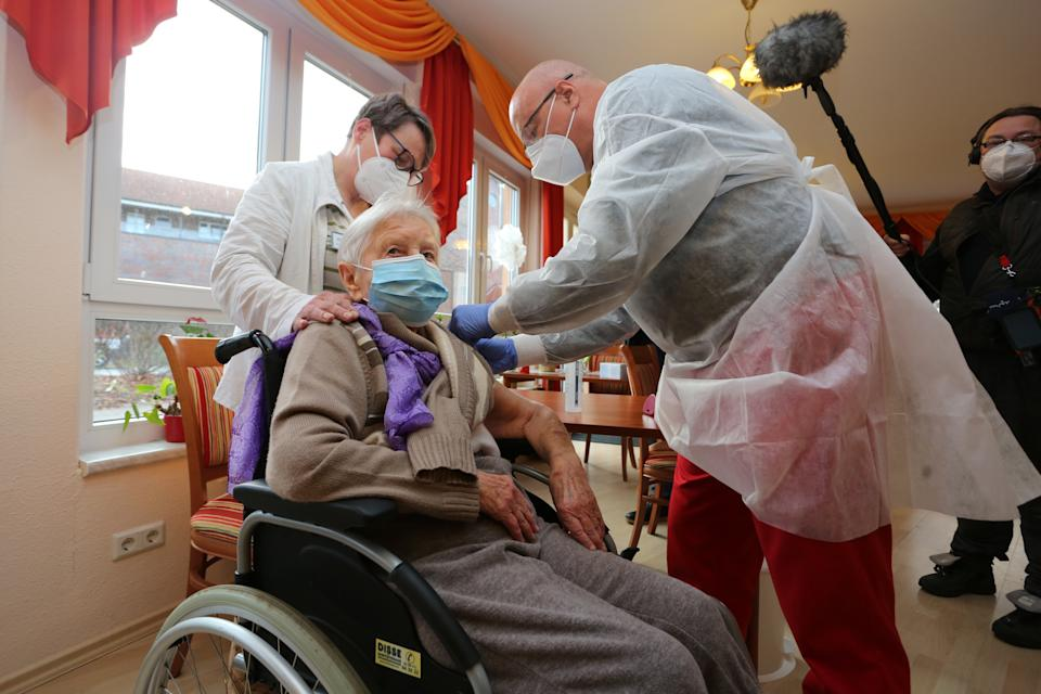 26 December 2020, Saxony-Anhalt, Halberstadt: Nursing home resident Edith Kwoizalla, who is 101 years old, was the first to be vaccinated against Corona on Saturday before the official start of vaccination in Germany. IIn the district of Harz in a senior care facility in Halberstadt (Seniorenzentrum Krüger) the first residents as well as the nursing staff were vaccinated with the Covid-19 vaccine from Pfizer-Biontech. The physician Dr. Bernhard Ellendt (right) performed the vaccination. Photo: Matthias Bein/dpa-Zentralbild/dpa (Photo by Matthias Bein/picture alliance via Getty Images)