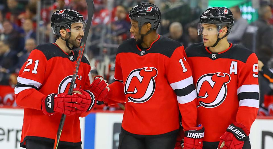 NEWARK, NJ - OCTOBER 17:  New Jersey Devils center Kyle Palmieri (21), New Jersey Devils right wing Wayne Simmonds (17) and New Jersey Devils left wing Taylor Hall (9) talk during the first period of the National Hockey League game between the New Jersey Devils and the New York Rangers on October 17, 2019 at the Prudential Center in Newark, NJ.  (Photo by Rich Graessle/Icon Sportswire via Getty Images)