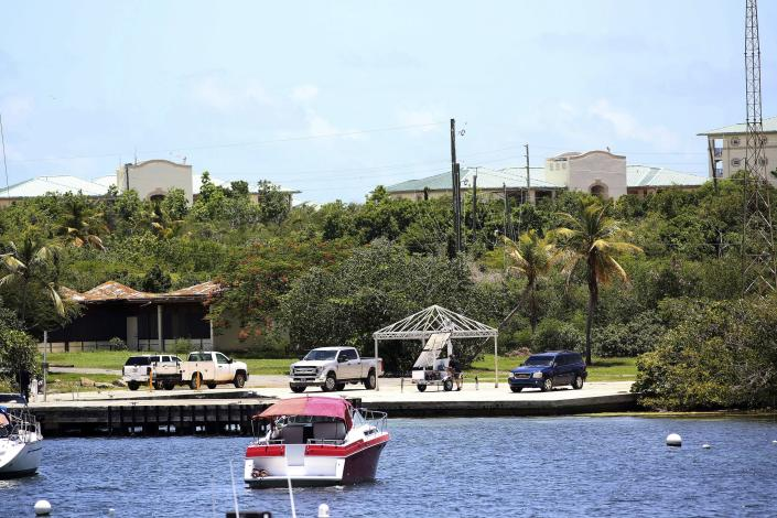 Vehicles are parked on a government dock in Red Hook where FBI agents were seen last Monday boarding a boat, in St. Thomas, U.S. Virgin Islands, Wednesday, Aug. 14, 2019. Curiosity in St. Thomas peaked this week as a group of FBI agents descended on nearby Little St. James Island and carried away what locals say were several large items from one of two islands that the 66-year-old Jeffery Epstein owned. (AP Photo/Gabriel Lopez Albarran)