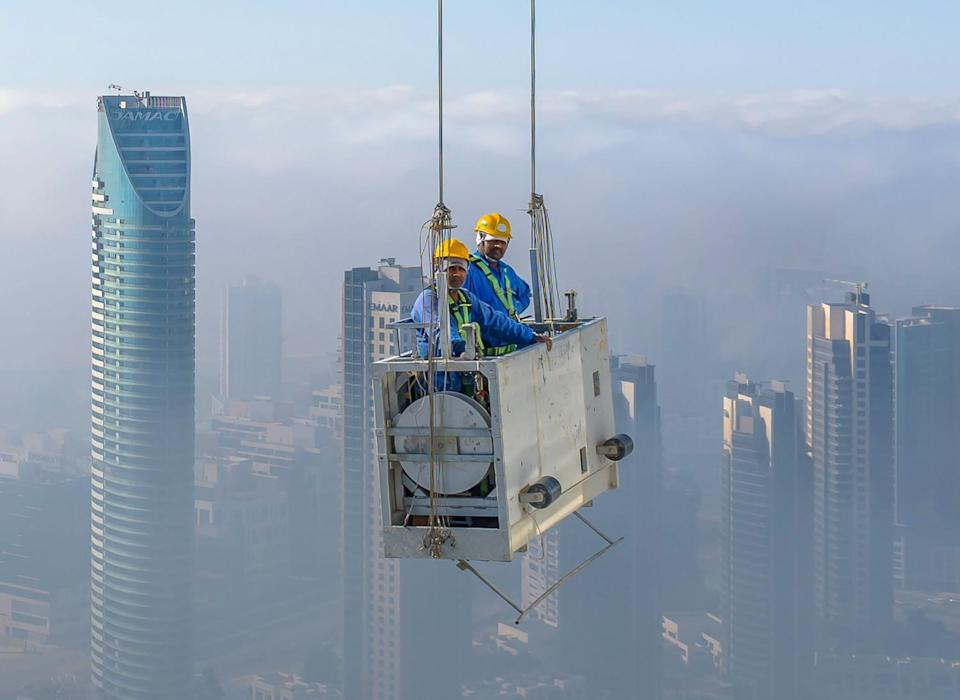 The pair were given an unimpeded view of the city through the morning fog as they went about their work. (SWNS)