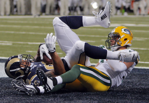 St. Louis Rams tight end Lance Kendricks, left, lands in the end zone after catching an 11-yard touchdown pass as Green Bay Packers cornerback Micah Hyde defends during the second quarter of a preseason NFL football game Saturday, Aug. 16, 2014, in St. Louis. (AP Photo/Scott Kane)