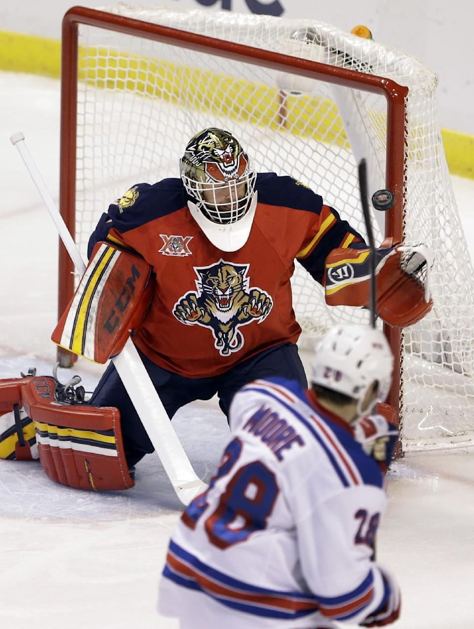A shot by New York Rangers center Dominic Moore (28) against Florida Panthers goalie Tim Thomas, hits the cross bar during the first period of an NHL hockey game Tuesday, Dec. 31, 2013, in Sunrise, Fla. (AP Photo/Wilfredo Lee)