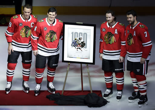 Chicago Blackhawks' Chris Kunitz, second from left, Jonathan Toews, left, Duncan Keith, second from right, and Brent Seabrook pose for photos before an NHL hockey game against the New Jersey Devils, Thursday, Feb. 14, 2019, in Chicago. Kunitz, will play his 1,000th NHL game on Thursday against the Devils. (AP Photo/Nam Y. Huh)