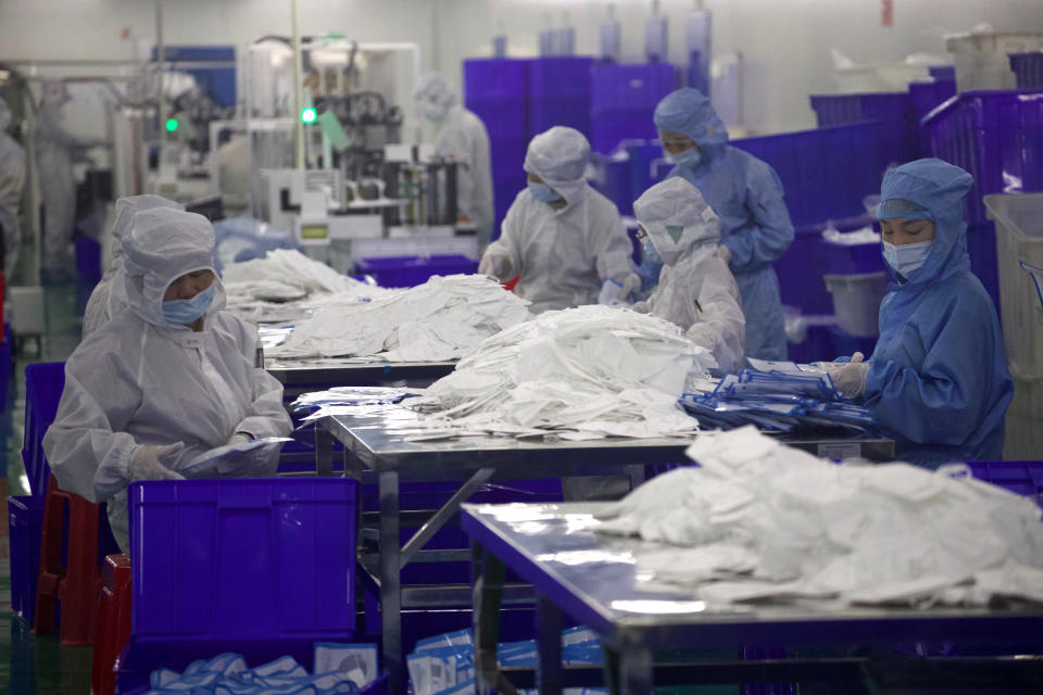Workers labor in a clean room producing masks at a production line for the Wuhan Zonsen Medical Products Co. Ltd in Wuhan in central China's Hubei province on Sunday, April 12, 2020. Chinese regulators say ventilators, masks and other supplies being exported to fight the coronavirus will be subject to quality inspections following complaints shoddy or substandard goods were being sold abroad. (AP Photo/Ng Han Guan)