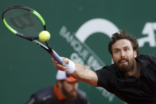 Ernests Gulbis of Latvia returns a ball to Alexander Zverev of Germany during their second round match at the ATP 250 Geneva Open tournament in Geneva, Switzerland, Tuesday, May 21, 2019. (Salvatore Di Nolfi/Keystone via AP)