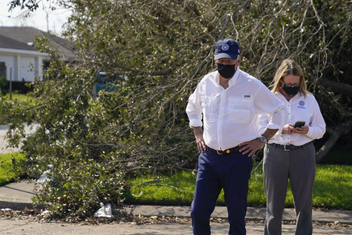 President Joe Biden pauses as he tours a neighborhood impacted by Hurricane Ida, Friday, Sept. 3, 2021, in LaPlace, La., as Federal Emergency Management Agency Administrator Deanne Criswell checks her phone. (AP Photo/Evan Vucci)