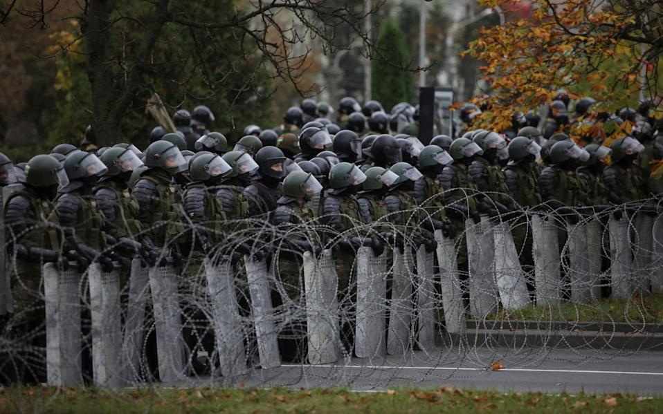 Belarusian service members stand guard during an opposition rally to reject the presidential election results - REUTERS