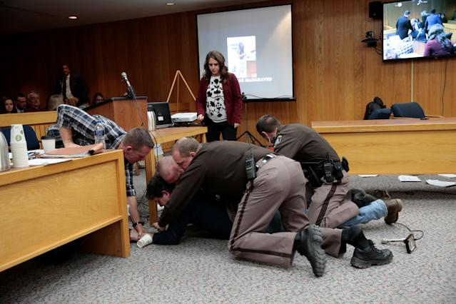 Randall Margraves (2nd L) is tackled after he lunged at Larry Nassar (not seen) a former team USA Gymnastics doctor who pleaded guilty in November 2017 to sexual assault charges, during victim statements of his sentencing in the Eaton County Circuit Court in Charlotte, Michigan, U.S., February 2, 2018. Picture 7 of 10 in series. REUTERS/Rebecca Cook