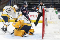 Columbus Blue Jackets' Jack Roslovic, top, scores a goal against Nashville Predators' Juuse Saros, front, as Alexandre Carrier defends during the second period of an NHL hockey game Wednesday, May 5, 2021, in Columbus, Ohio. (AP Photo/Jay LaPrete)