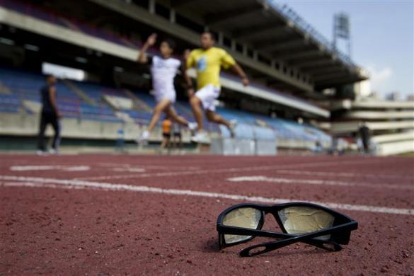 A pair of sunglasses, covered with tape, is seen on the track as its owner, a blind runner (back) from the Venezuelan Paralympics team, trains with a guide in Caracas April 17, 2012.