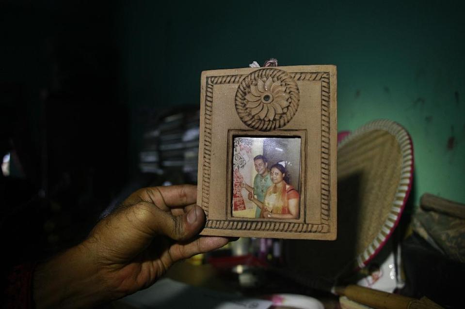 A family photograph of Bangladeshi blogger Niloy Chakrabarti, who used the pen-name Niloy Neel, with his wife is held up in their home in Dhaka on August 7, 2015 (AFP Photo/Suvra Kanti Das)