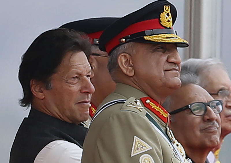 In this March 23, 2019 photo, Pakistan's Army Chief Gen. Qamar Javed Bajwa, center, watches a parade with Prime Minister Imran Khan, left, and President Arif Alvi, in Islamabad, Pakistan. Khan is keeping his powerful army chief in place for another three years, amid heightened tensions with India over Kashmir as well as the end of U.S.-Talban peace talks for neighboring Afghanistan. Khan postponed the retirement of Bajwa on Monday, Aug. 19, 2019. (AP Photo/Anjum Naveed)